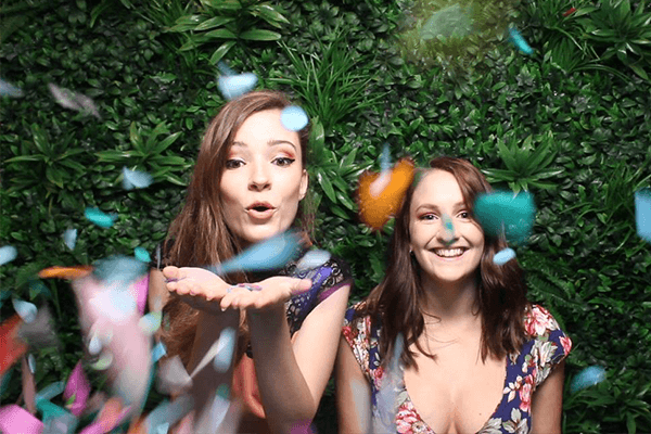 two girls throwing confetti in front of a greenwall backdrop