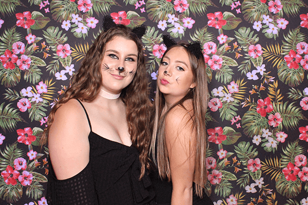 two girls in front of our dark floral backdrop